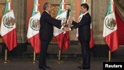 El presidente saliente, Felipe Calderón (izq.), entrega a Enrique Peña Nieto la enseña nacional durante la toma de posesión.