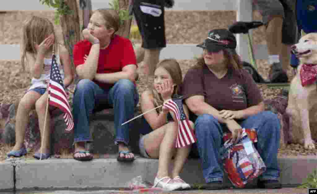 A family watches as floats and other entrees roll by during the 63rd Annual Boulder City Damboree Parade, Monday, July 4, 2011, in Boulder City, Nev. (AP Photo/Julie Jacobson)