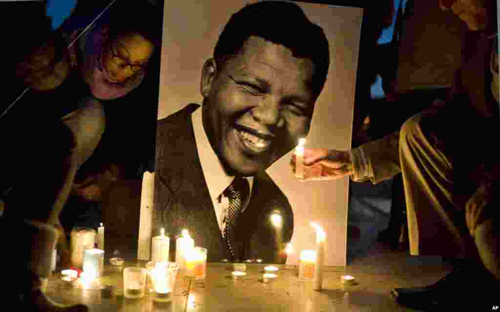 People light candles in front of a photo of former South African president Nelson Mandela, at the Trocadero Square, Paris,  France, Dec. 15, 2013.