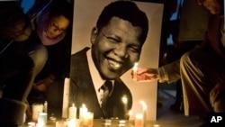 Warga menyalakan lilin di depan foto mantan presiden Afrika Selatan Nelson Mandela di Trocadero Square, Paris.