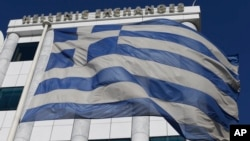 A Greek flag waves outside the Stock Exchange in Athens on Monday, Dec. 29, 2014.