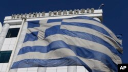 FILE - A Greek flag flutters outside the Stock Exchange in Athens Dec. 29, 2014. Decisions, made in the throes of a growing debt crisis, contributed to a program that proved unsustainable, an IMF review has found.