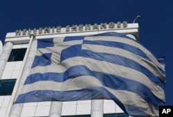 FILE - A Greek flag waves at the Stock Exchange in Athens. Greece will have early national elections Saturday, stoking investor concerns that the main opposition party will win and will want to renege on bailout terms.