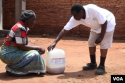 Founder of Urine for Wealth Project Goodfellow Phiri buying urine from a customer in the capital, Lilongwe. (L. Masina/VOA)
