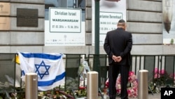 FILE - A man pays respects prior to a service for victims of a shooting — alleged to have been carried out in May by French-Algerian Mehdi Nemmouche — at the Jewish Museum in Brussels, June 2, 2014.