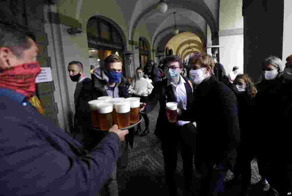 People line up for a beer at a restaurant terrace in Prague, Czech Republic.