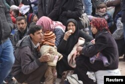 Syrians that evacuated the eastern districts of Aleppo rest while waiting to board buses, in a government-held area in Aleppo, Syria in this handout picture provided by SANA on Nov. 29, 2016.