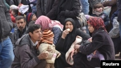 Syrians that evacuated the eastern districts of Aleppo rest while waiting to board buses, in a government-held area in Aleppo, Syria in this handout picture provided by SANA, Nov. 29, 2016.