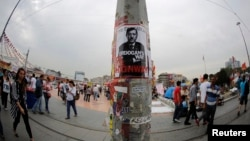 People walk past a poster depicting Turkish Prime Minister Tayyip Erdogan, put up by demonstrators, at Taksim Square in Istanbul June 7, 2013.