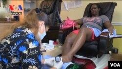 Thợ làm nail đang phục vụ khách trong một salon ở Mỹ.