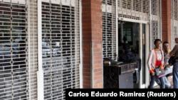 Una mujer sale de un supermercado con las rejas parcialmente cerradas como precaución contra disturbios o saqueos, en San Cristóbal, Venezuela, 16 de enero de 2018. REUTERS/Carlos Eduardo Ramirez.