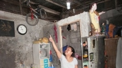 Sheila Royeras admires the soda bottle solar bulbs that were installed in her home in Manila, Philippines. The bulbs are made out of a soda bottle, purified water and some bleach.