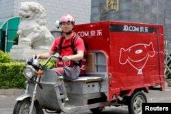 中国电子商务公司京东的首席执行官兼创始人刘强东2014年6月16日在北京开电动三轮车为客户送货,这是为了纪念公司成立日。