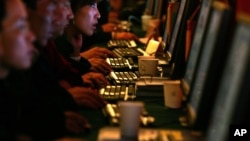 Chinese are seen working on computer work stations. Called 'bo ke' in Chinese, blogs are hugely popular, especially among the young, despite strict rules on content enforced by the government.