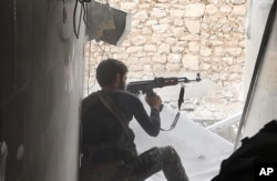 FILE - This undated file photo posted Nov. 4, 2014, by the Raqqa Media Office of the Islamic State group, a militant extremist group, shows an Islamic State fighter in Kobani, Syria.