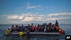 Relawan dari regu penyelamat Barcelona, Spanyol, membantu menurunkan perahu kecil saat para pengungsi turun dari perahu yang membawa mereka dari pantai Turki tiba di pulau Lesbos, Yunani timur laut, Rabu dini hari, 7 Oktober 2015. (Foto: dok).