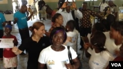 Jamilah Jawara, seorang penyintas Ebola, menari merayakan kesembuhannya dengan penyintas lain, di Kenema, Sierra Leone (17/10). (VOA/Nina deVries)