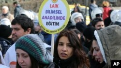 "FILE - A woman holds a placard demanding ""a secular and science-based education system"" as hundreds of students and teachers march in Ankara, Feb. 13, 2015."