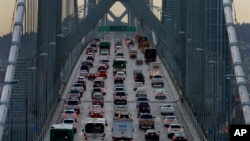 In this Dec. 10, 2015, file photo, vehicles make their way westbound on Interstate 80 across the San Francisco-Oakland Bay Bridge. California wants to fight the Trump administration's move to revoke the state's authority to set auto mileage standards. (AP Photo/Ben Margot, File)