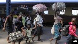 FILE: Women and children carry baggage at the main train station in Harare. (AP Photo/Tsvangirayi Mukwazhi)