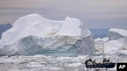 ເຮືອຫາປາລຳນຶ່ງ ຢູ່ໃນເຂດໜ້ານໍ້າ ທີ່ເຕັມໄປດ້ວຍນໍ້າກ້ອນ ທີ່ແຕກອອກມາຈາກແຜ່ນນໍ້າກ້ອນຂະໜາດໃຫຍ່ ໃກ້ໆເມືອງ Ilulissa ຂອງ Greenland (18 ກໍລະກົດ 2011)