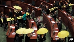 "Pro-democracy legislators hold up yellow umbrellas and banners stating ""I want real universal suffrage"" and ""Leung Chun-ying Step down"" as they walk out of the Legislative Council during Hong Kong Chief Executive Leung Chun-ying's annual policy address in"