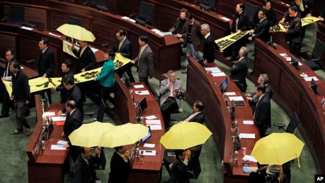 Các nhà lập pháp thân dân chủ giương dù vàng và bỏ ra ngoài trong lúc Trưởng quan hành chính Hồng Kông Lương Chấn Anh đọc diễn văn, ngày 14/1/2014.