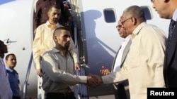 Jordanian peacekeepers Hasan Al-Mazawdeh (front) and Qasim Al-Sarhan are welcomed by officials as they arrive at Khartoum Airport, January 2, 2013, after 136 days of captivity in Sudan's Darfur region according to local media.