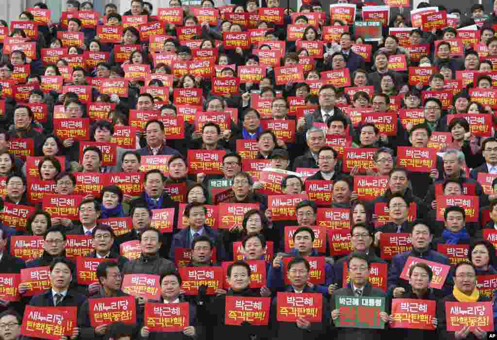 Lawmakers and members of opposition parties hold cards during a rally demanding the impeachment of South Korean President Park Geun-hye at the National Assembly in Seoul.