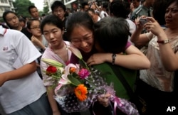 FILE - A Chinese student is greeted by a relative after taking the annual college entrance examinations in Beijing, June 8, 2010.