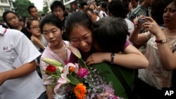 "FILE - A Chinese student is greeted by a relative after taking the annual college entrance examinations in Beijing, June 8, 2010. Each year, about 10 million high school seniors across China take the ""gaokao"", the exam that is the sole determinant for whe"