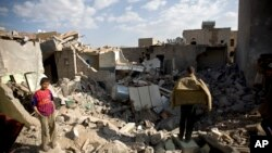 Anak-anak laki-laki Yaman berkumpul di sekitar rumah-rumah yang roboh karena hantaman serangan udara pasukan Arab Saudi di dekat bandara Sanaa, Yaman, 31 Maret 2015 (AP Photo/Hani Mohammed)