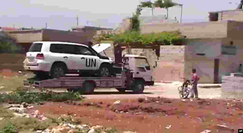 This image made from amateur video shows a towed U.N. observer car in Idlib, Khan Sheikhoun, Syria. (Shaam News Network via AP video)