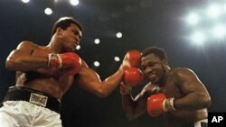 FILE - In this Jan. 28, 1974, file photo, Muhammad Ali, left, and Joe Frazier fight in a 12-round non-title fight at Madison Square Garden in New York. Former heavyweight champion Joe Frazier is seriously ill with liver cancer. His personal and business m