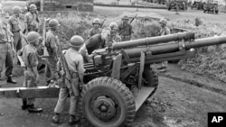 Gen. Maxwell Taylor, President John F. Kennedy's special military adviser, examines a South Vietnamese cannon during a tour of the border between North and South Vietnam, Oct. 22, 1961.