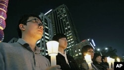 South Koreans take a moment of silence for South Korean marines killed in a North Korean bombardment of a South Korean island, 23 Nov 2010