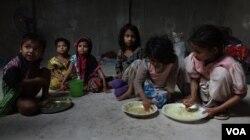 Some Rohingya refugee children taking their meals inside a refugee camp in West Bengal. (Shaikh Azizur Rahman/VOA)