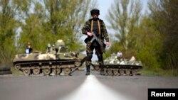 Binh sĩ Ukraine đứng gác trước xe bọc thép tại một chốt kiểm soát gần làng Malinivka, miền đông Ukraine.