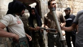 Free Syrian Army fighters display what they said were shells used by forces loyal to Syria's President Bashar al-Assad during clashes with them in Aleppo's Karm al-Jabal district, June 2, 2013.