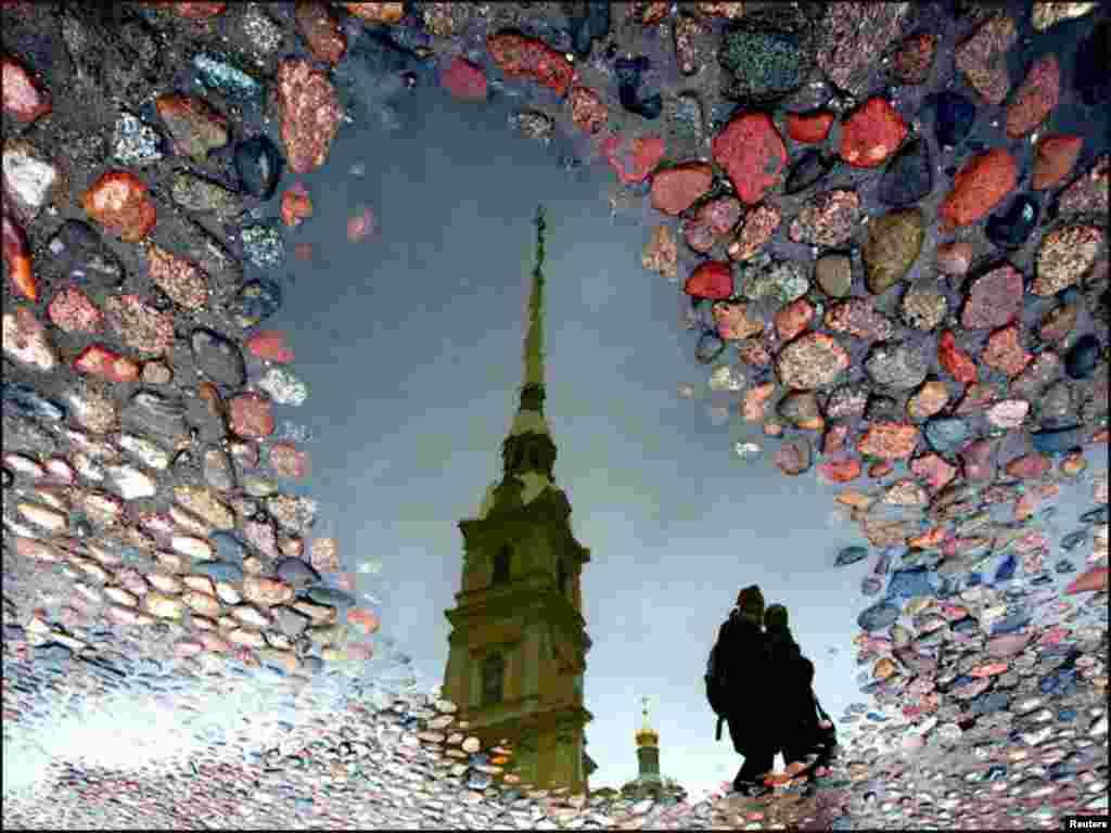 روس کے شہر سینٹزبرگ میں سیاحوں کو پانی کے عکس سے نمایاں ایک تصویر۔