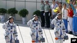 Ba phi hành gia Trung Quốc (từ trái sang phải) Liu Yang, Jing Haipeng và Liu Wang chào trước khi đi vào phi thuyền Thần Châu 9, ngày 16 tháng 6, 2012