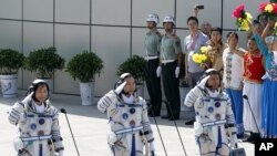 China's astronauts from left Liu Yang, Jing Haipeng and Liu Wang salute before they depart for the Shenzhou 9 spacecraft rocket launch pad at the Jiuquan Satellite Launch Center in Jiuquan, China, Saturday, June 16, 2012.