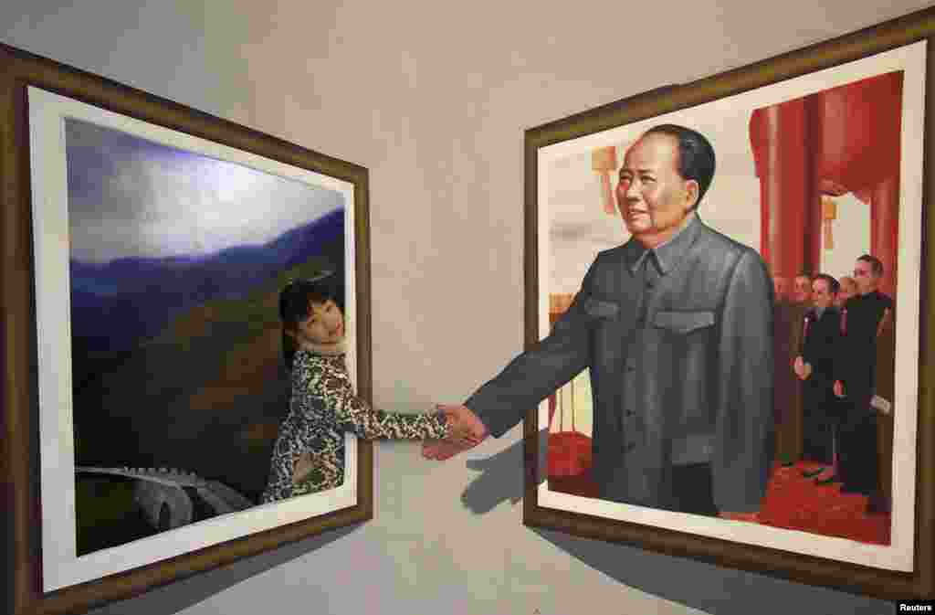 A girl poses for a photograph next to a 3D painting of China's late Chairman Mao Zedong at an exhibition in Binzhou, Shandong province, Dec. 15, 2013.