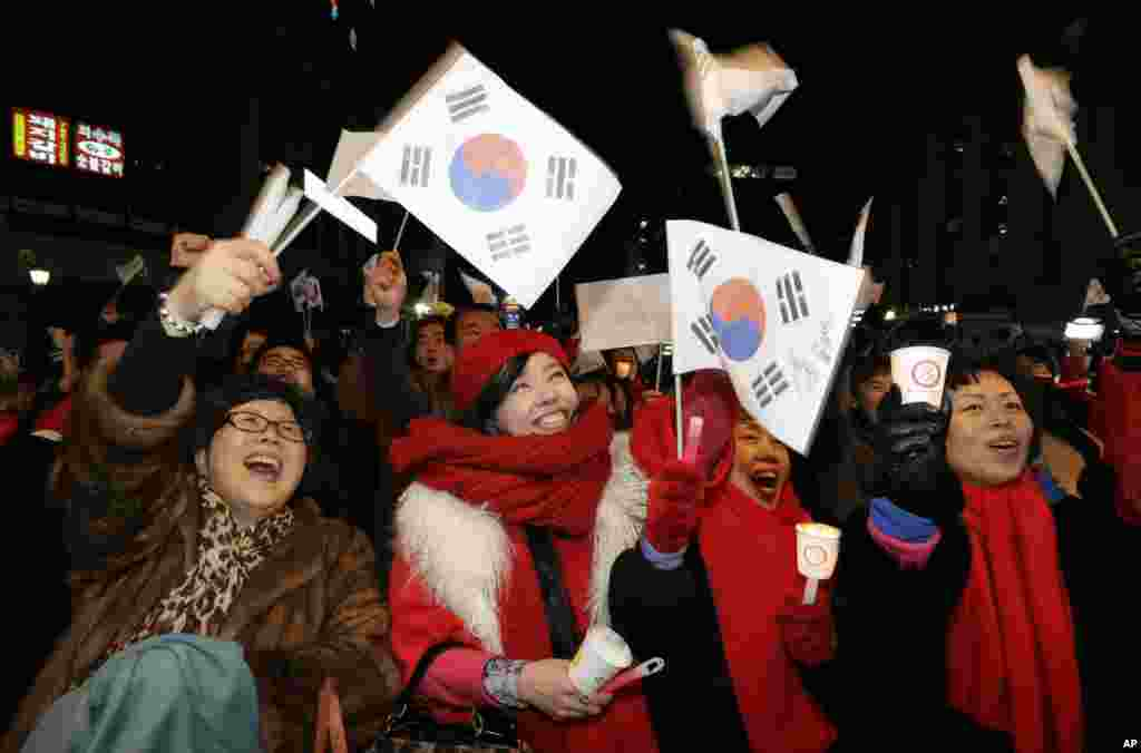 Supporters of Park Geun-hye cheer near her Saenuri Party's head office in Seoul, December 19, 2012.