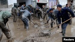 Regu penyelamat dan warga bekerjasama membersihkan lumpur di sebuah bangunan wilayah Minxian, provinsi Gansu (13/5). Sekitar 40 korban dilaporkan tewas dan 18 orang lainnya dinyatakan hilang pasca badai melanda daerah ini sehari sebelumnya.