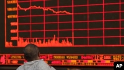 FILE - An investor watches as the Shanghai Composite Index falls at a brokerage in Beijing, China, May 6, 2019. The coronavirus outbreak has caused an economic ripple effect throughout Asia.