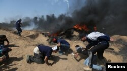Palestinian demonstrators take cover from Israeli gunfire during a protest marking Jerusalem Day at the Israel-Gaza border in the southern Gaza Strip, June 8, 2018.