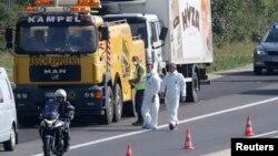 Тягач собирается оттянуть с шоссе грузовик, в котором были обнаружены тела мигрантов. Город Парндорф, Австрия. 27 августа 2015 г.