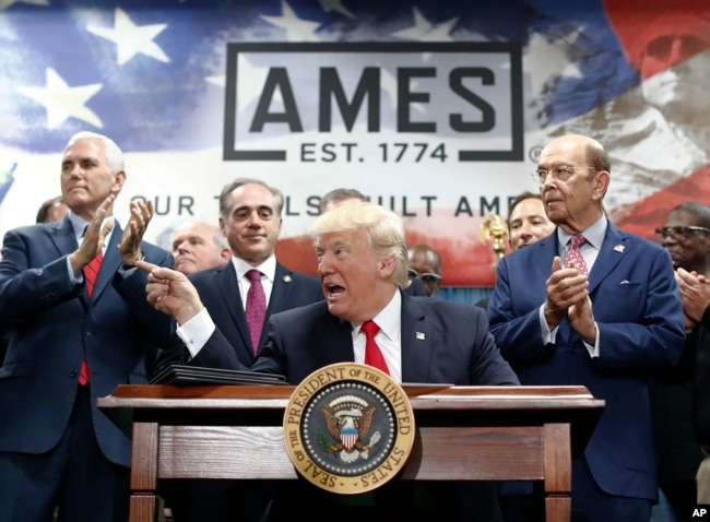 President Donald Trump, joined by Vice President Mike Pence (from left), Secretary of Veterans Affairs David Shulkin, and Wilbur Ross United States Secretary of Commerce, signs an Executive Order on the Establishment of Office of Trade and Manufacturing Policy at The AMES Companies, Inc., in Harrisburg, Pa., April, 29, 2017.