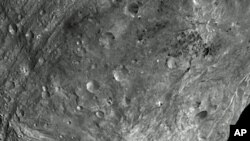 In this image, obtained by Dawn's framing camera, a peak at Vesta's south pole is seen at the lower right. The grooves in the equatorial region are about 10 kilometers wide. The image was taken on July 24, 2011, from a distance of about 5,200 kilometers